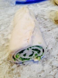 Flatten with a rolling pin. Add salt. Flatten salt. Add oil. Add chopped green onion and roll into a tube.